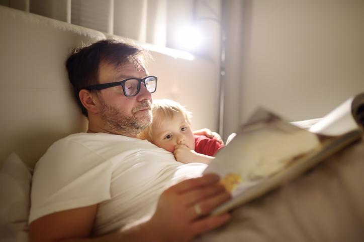 Papa qui lit une histoire à son enfant.