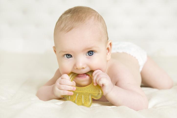 Bébé utilisant un anneau froid pour soulager ses dents.