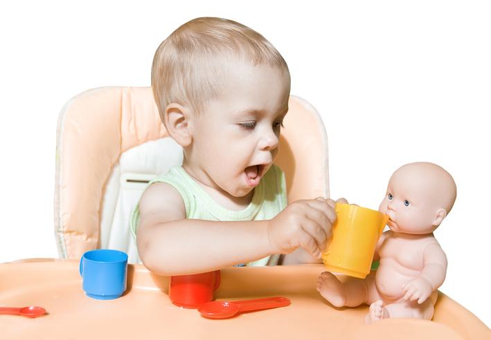 Enfant qui joue à la dinette avec une poupée