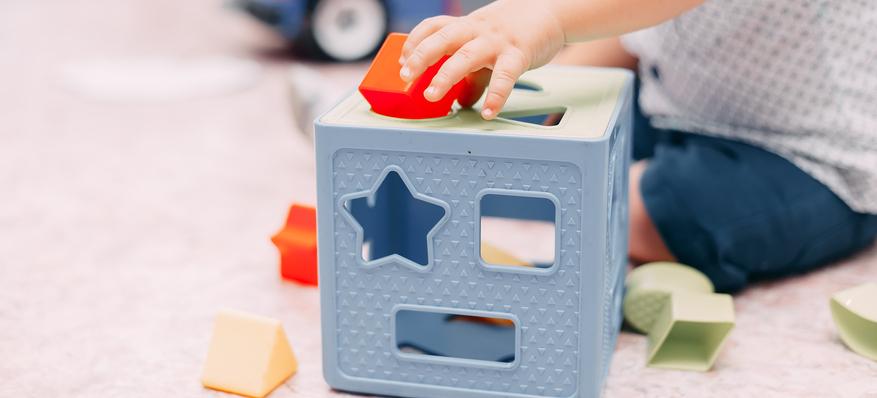 Enfant qui joue à faire entrer des formes dans des trous